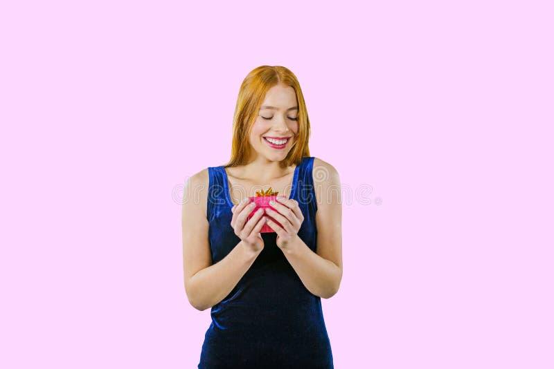 一件平衡的蓝色天鹅绒礼服的一个美丽的红发女孩拿着有礼物的一个小盒子,拥抱和害羞地 图库摄影