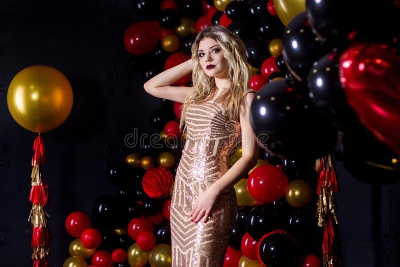 一件性感的礼服的美丽的女孩在一个演播室在轻快优雅背景中 免版税库存图片