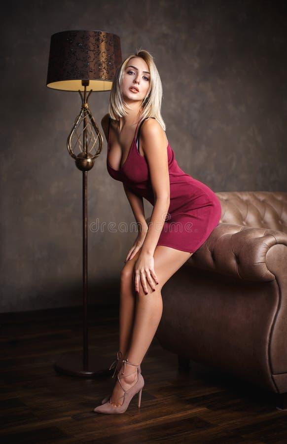 一件性感的礼服的美丽的白肤金发的女孩 免版税库存照片
