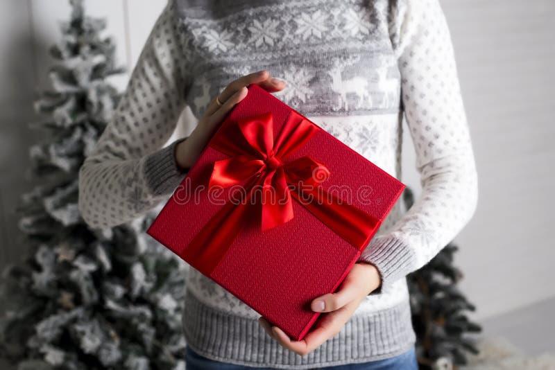 一件新年的毛线衣的女孩有鹿的在手中举行有礼物的一个红色箱子和一繁文缛节以冷杉木为背景 免版税库存照片