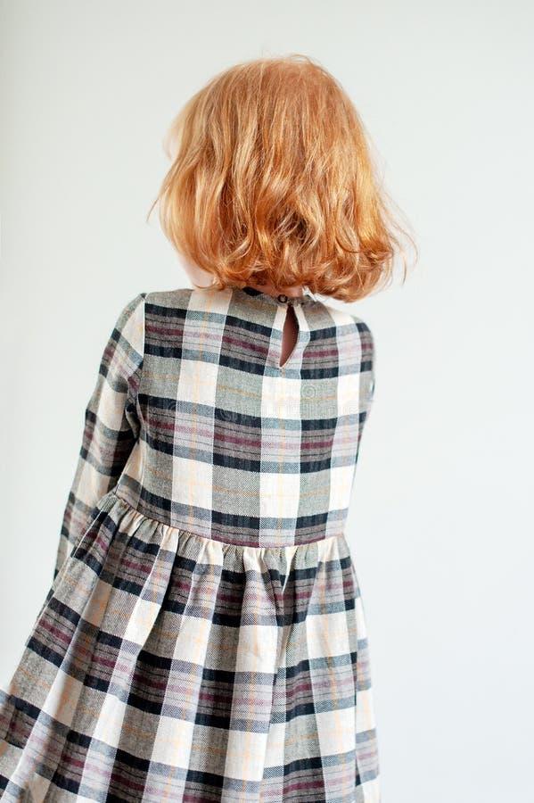 一件方格的礼服的一个女孩站立与她的后面 库存图片