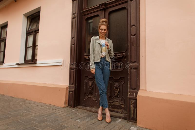 一件时兴的夹克的愉快的女孩有蓝色牛仔裤的 免版税库存照片