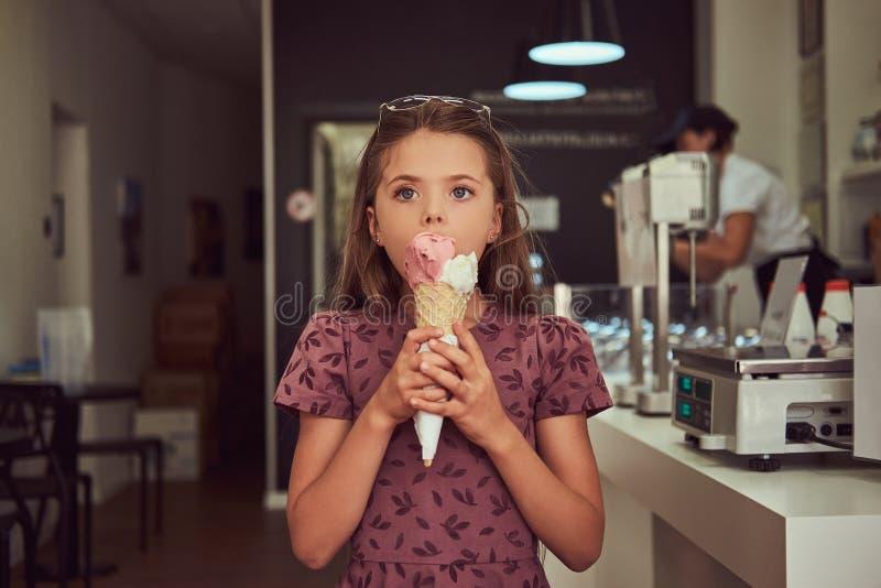 一件时兴的礼服的秀丽小女孩吃草莓的,站立在冰淇凌店里 免版税库存图片