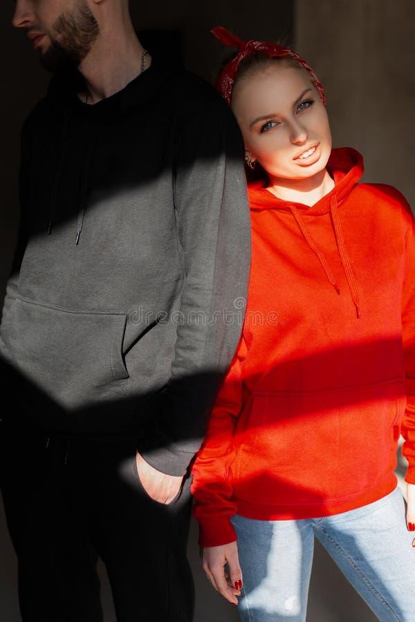 一件时兴的红色运动衫的快乐的俏丽的年轻白肤金发的妇女站立与有一个胡子的一个年轻残酷人在屋子里 免版税库存照片