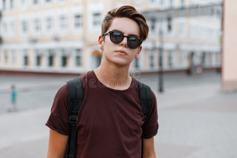 一件时兴的T恤杉的严肃的英俊的年轻行家人有与背包的一种时髦的发型的在街道上站立 库存图片