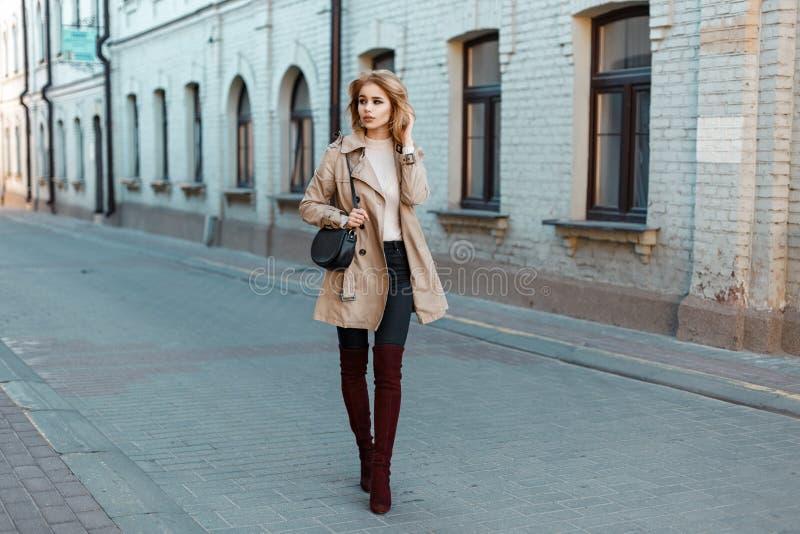 一件时髦外套的时髦的女孩和时兴的起动与 图库摄影