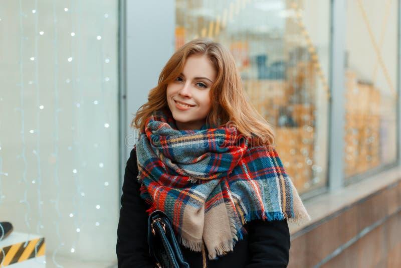 一件时髦的冬天外套的迷人的年轻女人在与葡萄酒羊毛围巾的黑手套在商店窗口附近站立 免版税库存图片