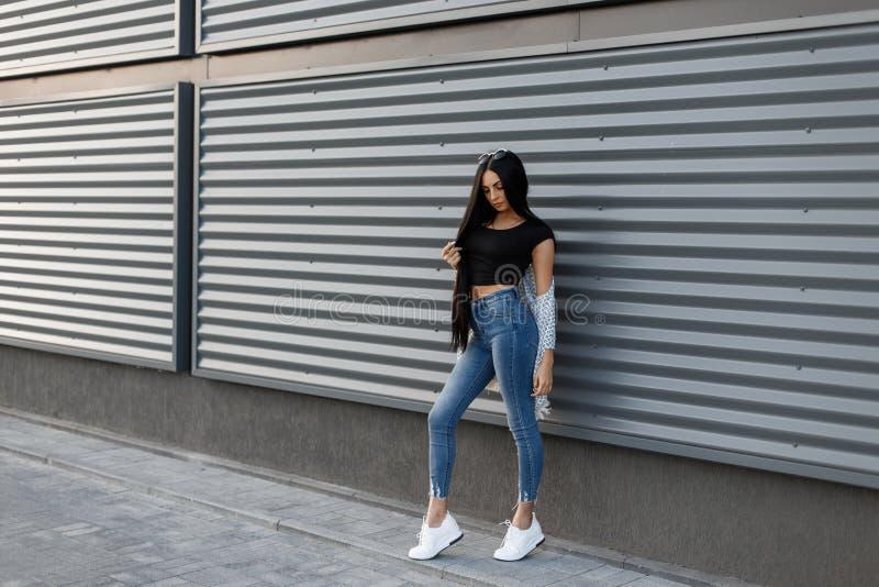 一件时髦的夹克的时髦的俏丽的美丽的年轻女人在时兴的蓝色牛仔裤的葡萄酒黑色上面在夏天运动鞋 免版税库存图片