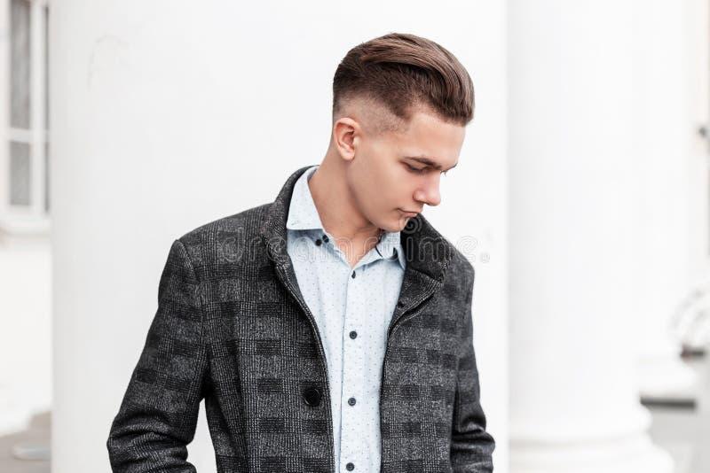 一件时髦的格子花呢披肩灰色夹克的企业年轻人有在一件经典衬衣的一种时兴的发型的站立 库存图片