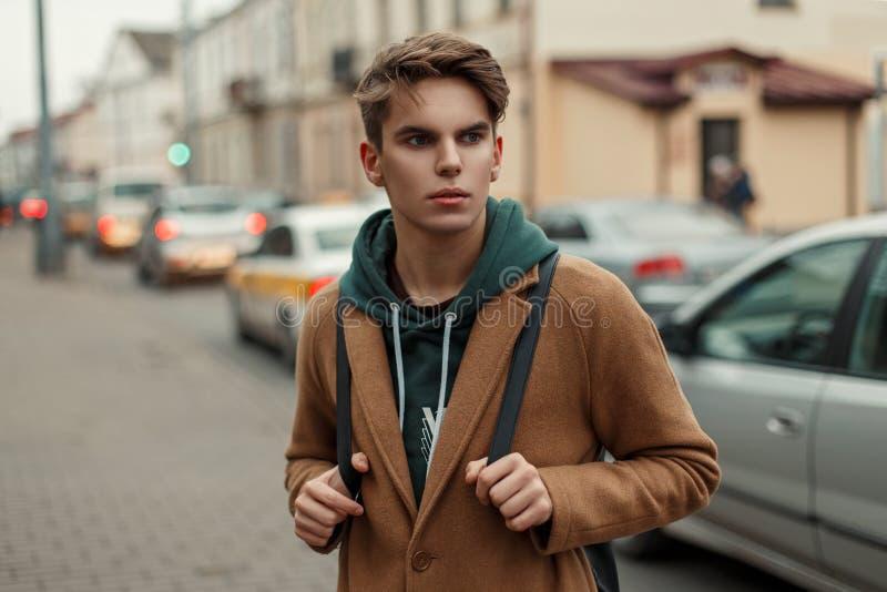一件时髦的葡萄酒外套的英俊的年轻人旅客与 免版税库存照片