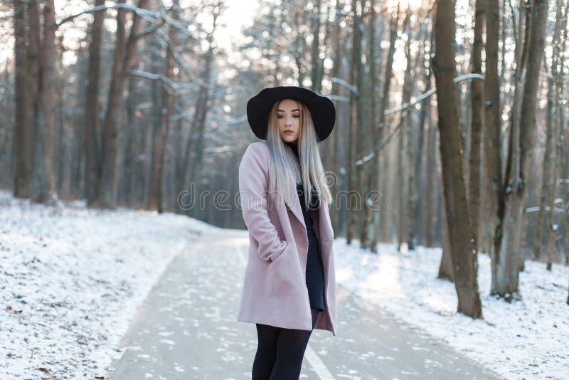 一件时髦的迷人的外套的时兴的年轻女人金发碧眼的女人在时髦的黑帽会议的一件黑礼服 免版税图库摄影
