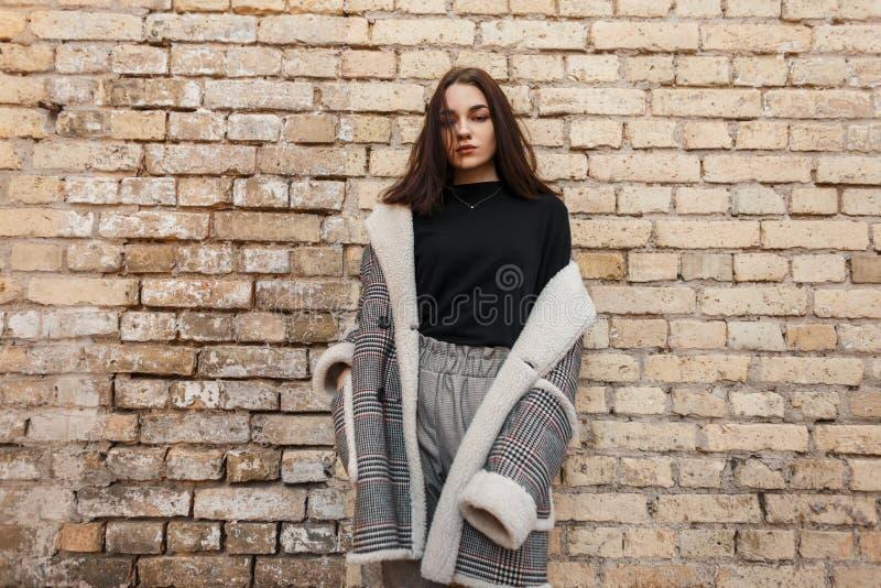 一件时髦黑T恤杉的俏丽的性感的年轻女人在灰色时髦的裤子姿势的一件豪华方格的外套 免版税库存照片