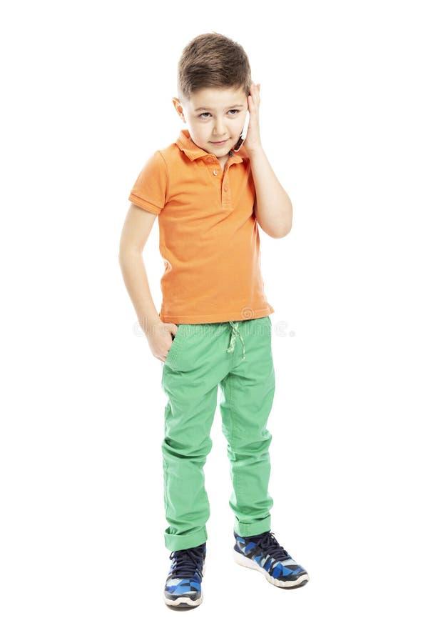 一件明亮的橙色马球T恤杉的一个逗人喜爱的学龄男孩在智能手机谈话 充分的高度 ?? r 图库摄影