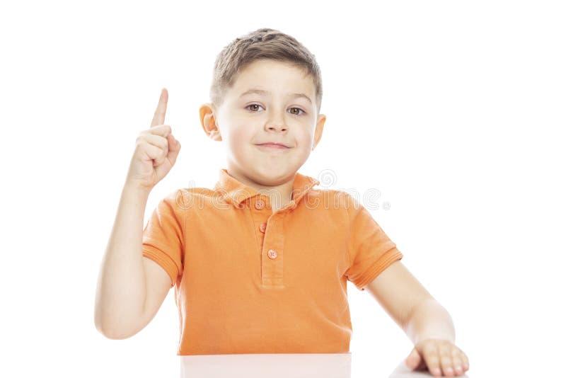 一件明亮的橙色马球T恤杉的一个逗人喜爱的学龄男孩坐在与他的赞许的桌上 r 在白色的Isolirvoan 免版税库存照片