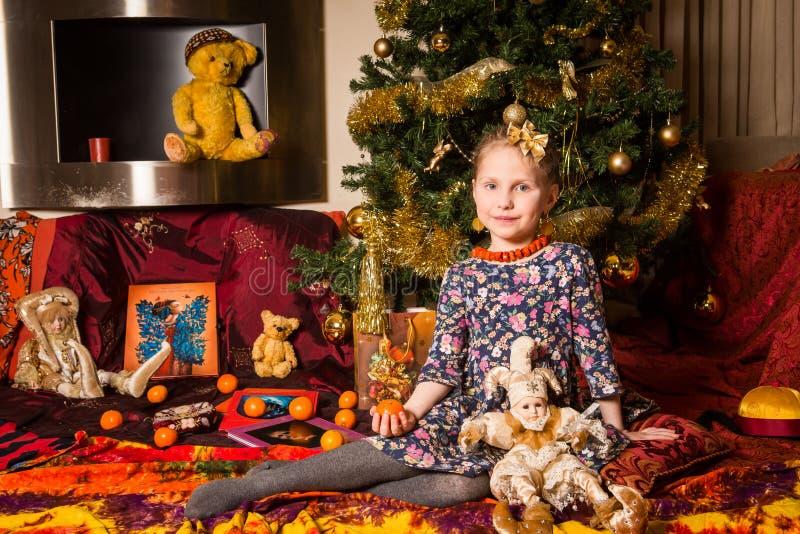 一件明亮的礼服的一个女孩在与手工制造玩偶的新年树附近坐 库存照片