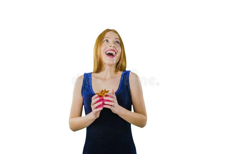 一件晚礼服的与一个箱子在她的手上微笑和查寻在的一个逗人喜爱的年轻红发女孩的画象 库存图片