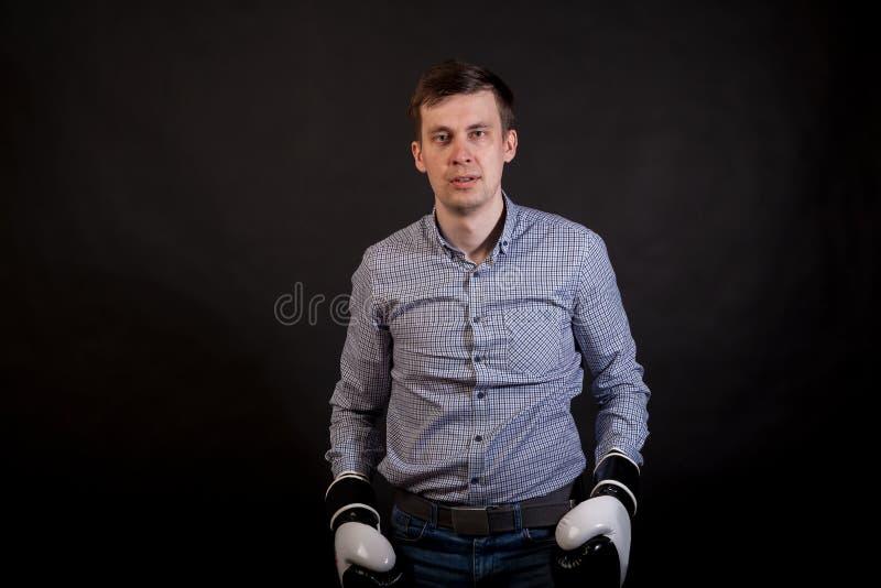 一件格子花呢上衣的深色头发的人有在他的手上的拳击手套的 免版税库存照片