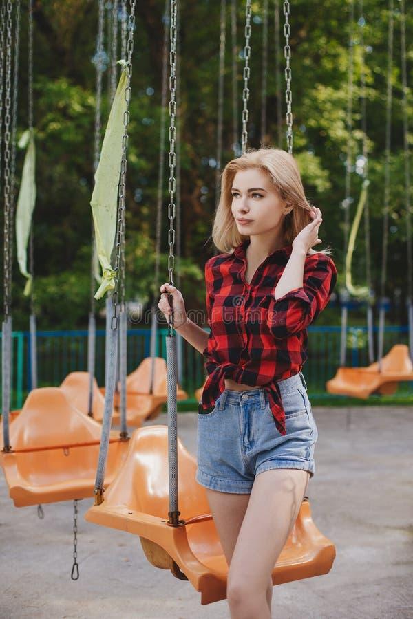 一件格子花呢上衣的白肤金发的女孩在公园 图库摄影