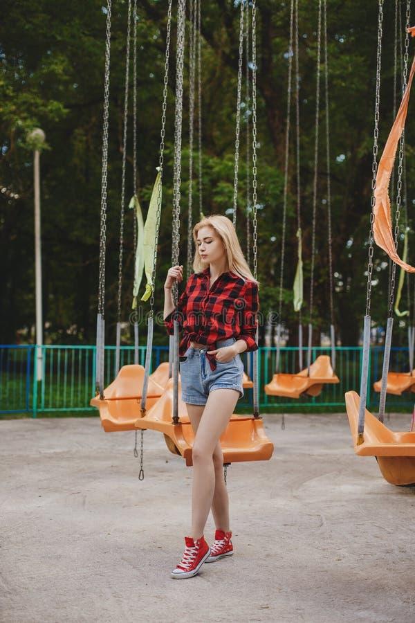 一件格子花呢上衣的白肤金发的女孩在公园 库存照片
