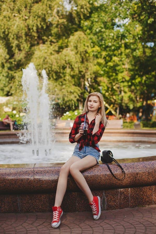 一件格子花呢上衣的白肤金发的女孩在喷泉 免版税图库摄影