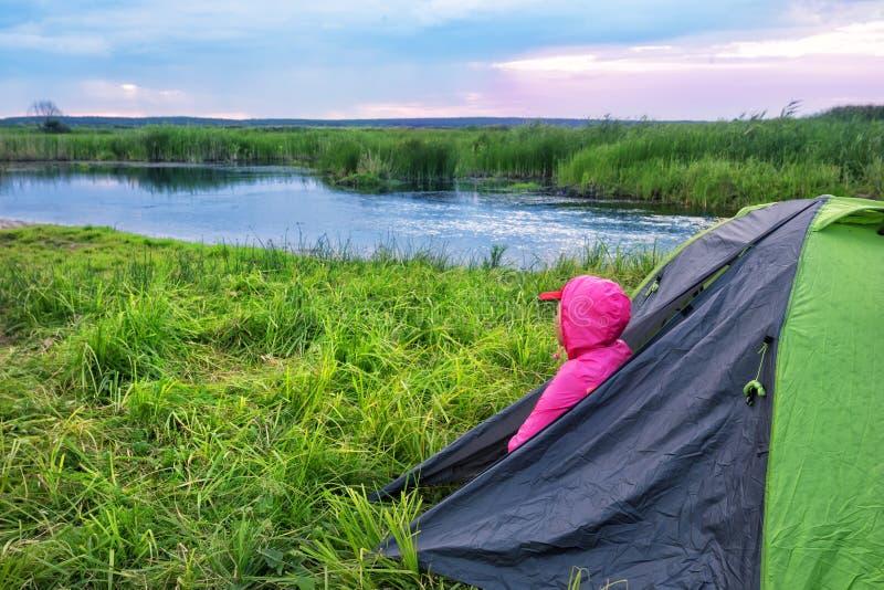 一件桃红色夹克的妇女有敞篷的注视着在帐篷外面黎明o 免版税库存图片