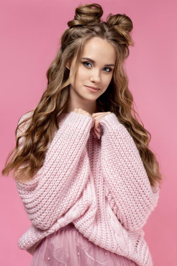 一件桃红色毛线衣的俏丽的少女在与理发和卷曲长发的桃红色背景 免版税库存照片