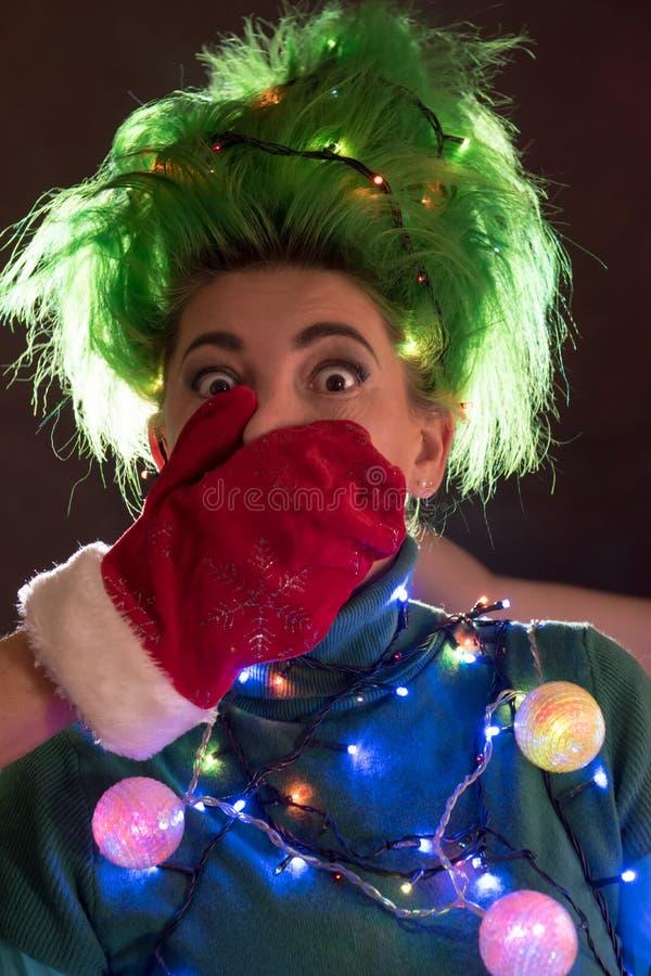一件桃红色礼服的一个美丽的女孩有绿色头发的装饰了自己与圣诞节诗歌选 她的头发是象圣诞树 的treadled 免版税图库摄影