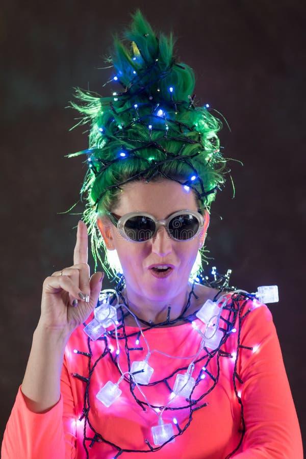 一件桃红色礼服的一个美丽的女孩有绿色头发的装饰了自己与圣诞节诗歌选 她的头发是象圣诞树 的treadled 库存图片