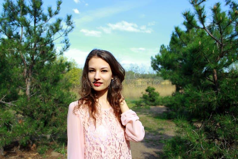 一件桃红色礼服的美丽的白肤金发的女孩,自然背景 免版税库存图片