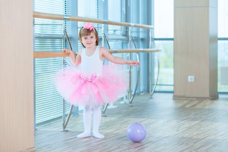 一件桃红色芭蕾舞短裙的小芭蕾舞女演员女孩 跳舞古典芭蕾的可爱的孩子在一个白色演播室 儿童舞蹈 孩子 库存照片