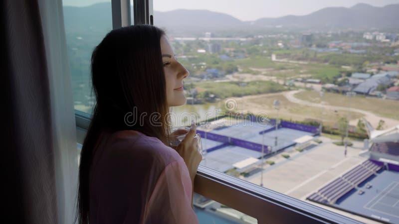 一件桃红色透明晨衣的妇女引人注意并且看入全景窗口和饮料咖啡 4k华欣 库存图片
