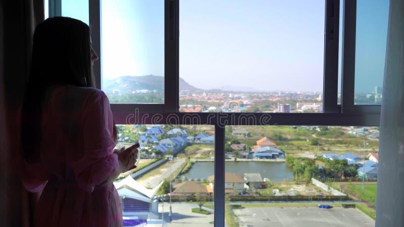 一件桃红色透明晨衣的妇女引人注意并且看入全景窗口和饮料咖啡 4k华欣 免版税库存图片
