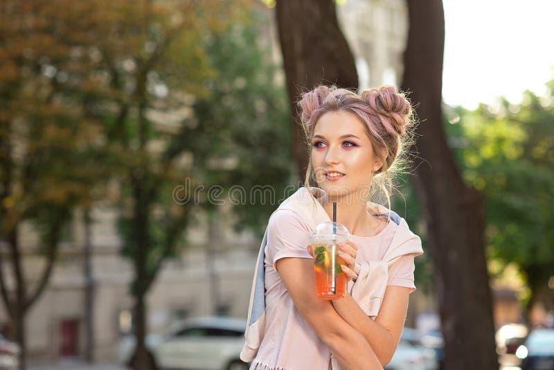 一件桃红色T恤杉和一件运动衫的愉快的年轻微笑女孩用坐外面与a的一个明亮的构成和头发小圆面包 免版税库存图片