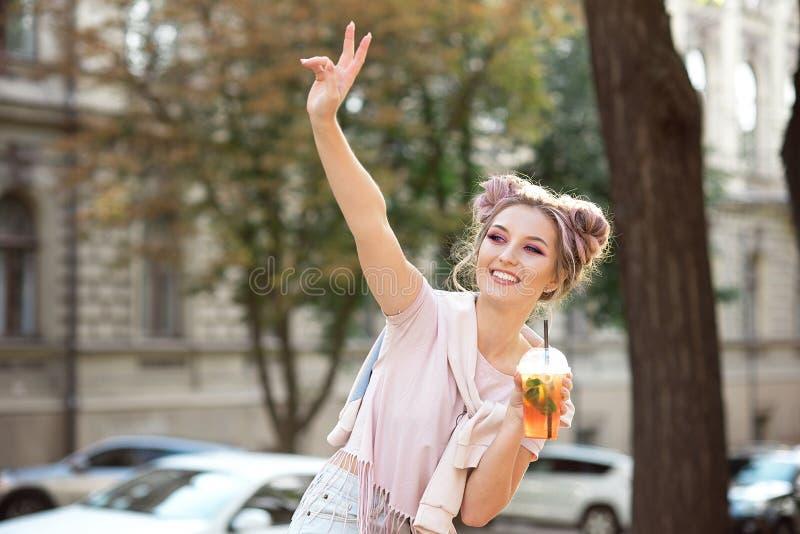 一件桃红色T恤杉和一件运动衫的愉快的年轻微笑女孩用坐外面与a的一个明亮的构成和头发小圆面包 图库摄影