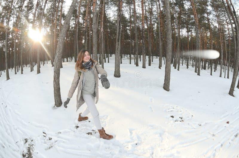 一件棕色外套的一个年轻和快乐的白种人女孩在一个积雪的森林里投掷一个雪球在冬天 与雪的比赛 图库摄影