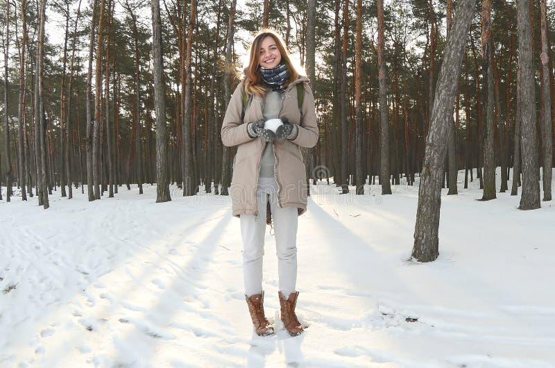 一件棕色外套的一个年轻和快乐的白种人女孩在一个积雪的森林里拿着一个雪球在冬天 Fisheye照片 库存照片