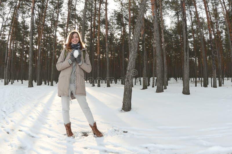 一件棕色外套的一个年轻和快乐的白种人女孩在一个积雪的森林里拿着一个雪球在冬天 Fisheye照片 库存图片