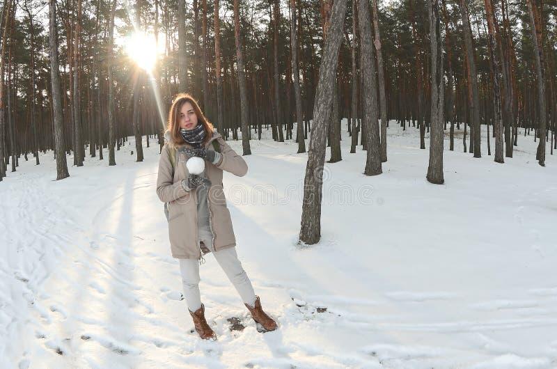 一件棕色外套的一个年轻和快乐的白种人女孩在一个积雪的森林里拿着一个雪球在冬天 Fisheye照片 免版税库存图片
