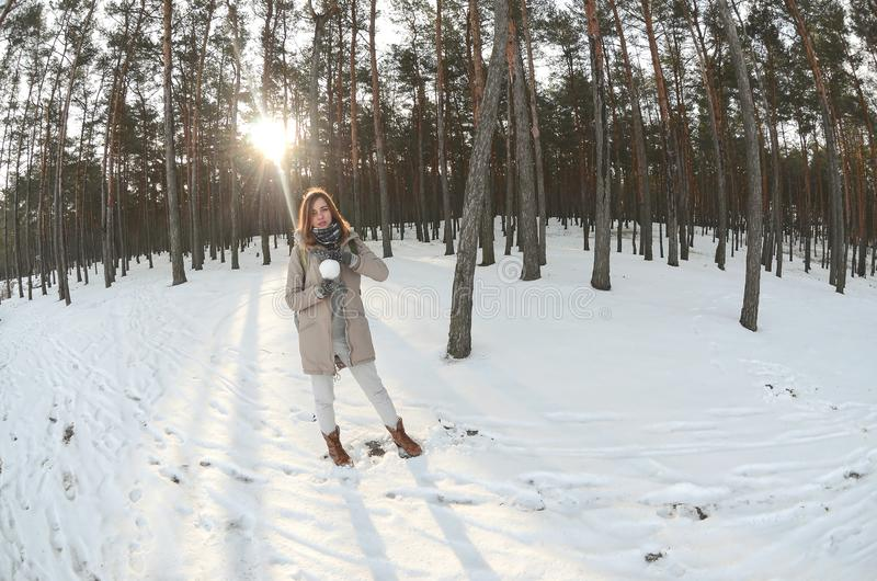 一件棕色外套的一个年轻和快乐的白种人女孩在一个积雪的森林里拿着一个雪球在冬天 Fisheye照片 免版税图库摄影