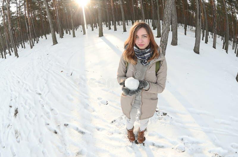 一件棕色外套的一个年轻和快乐的白种人女孩在一个积雪的森林里拿着一个雪球在冬天 Fisheye照片 免版税库存照片