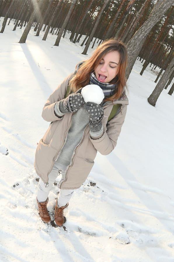 一件棕色外套的一个年轻和快乐的白种人女孩在一个积雪的森林里拿着一个雪球在冬天 Fisheye?? 免版税库存照片