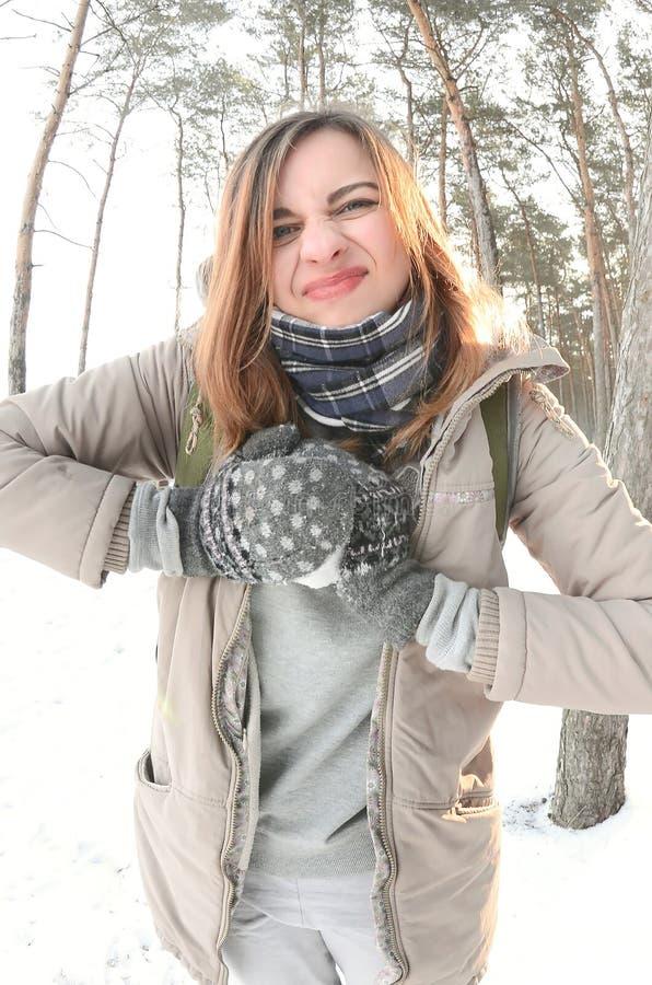 一件棕色外套的一个年轻和快乐的白种人女孩在一个积雪的森林里雕刻一个雪球在冬天 与雪的比赛在 免版税库存照片