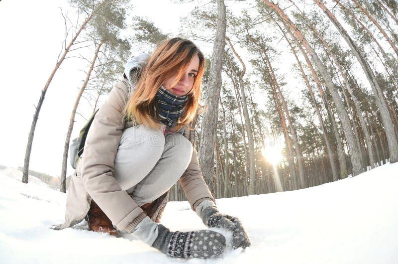 一件棕色外套的一个年轻和快乐的白种人女孩在一个积雪的森林里雕刻一个雪球在冬天 与雪的比赛在 库存图片