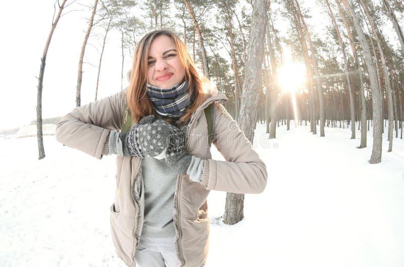 一件棕色外套的一个年轻和快乐的白种人女孩在一个积雪的森林里雕刻一个雪球在冬天 与雪的比赛在 免版税库存图片