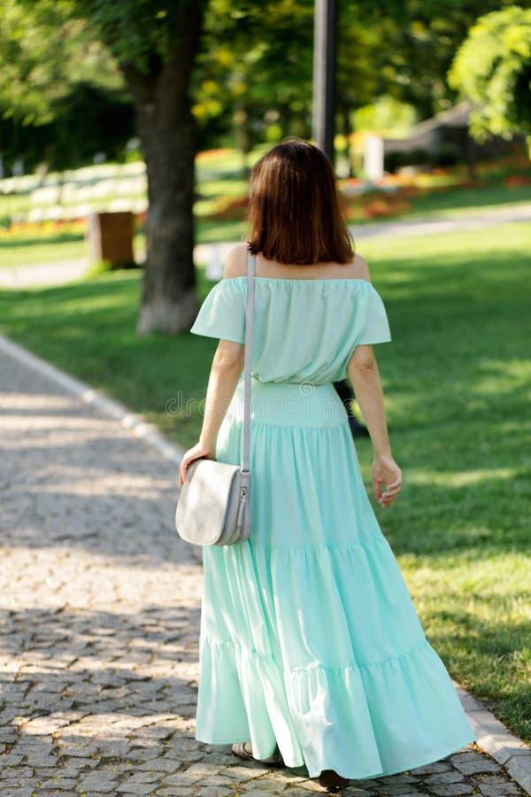 一件浅绿色的淡色长的礼服的年轻美丽的妇女是步行 免版税库存照片