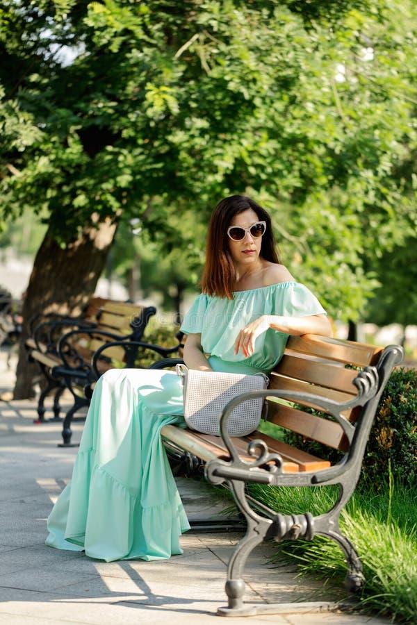 一件浅绿色的淡色长的礼服的年轻美丽的妇女是sitt 免版税库存图片