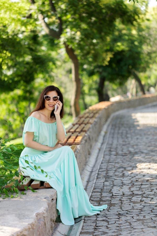 一件浅绿色的淡色长的礼服的年轻美丽的妇女是sitt 免版税库存照片