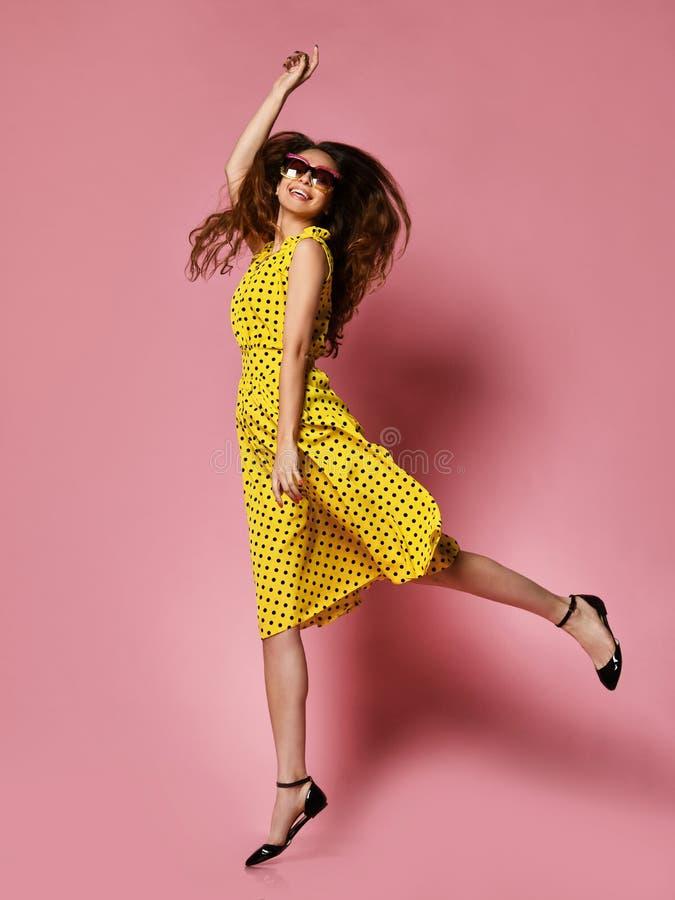 一件浪漫礼服的美女相当微笑在紫色背景的 在一件黄色圆点礼服的苗条卷曲女性模型 图库摄影