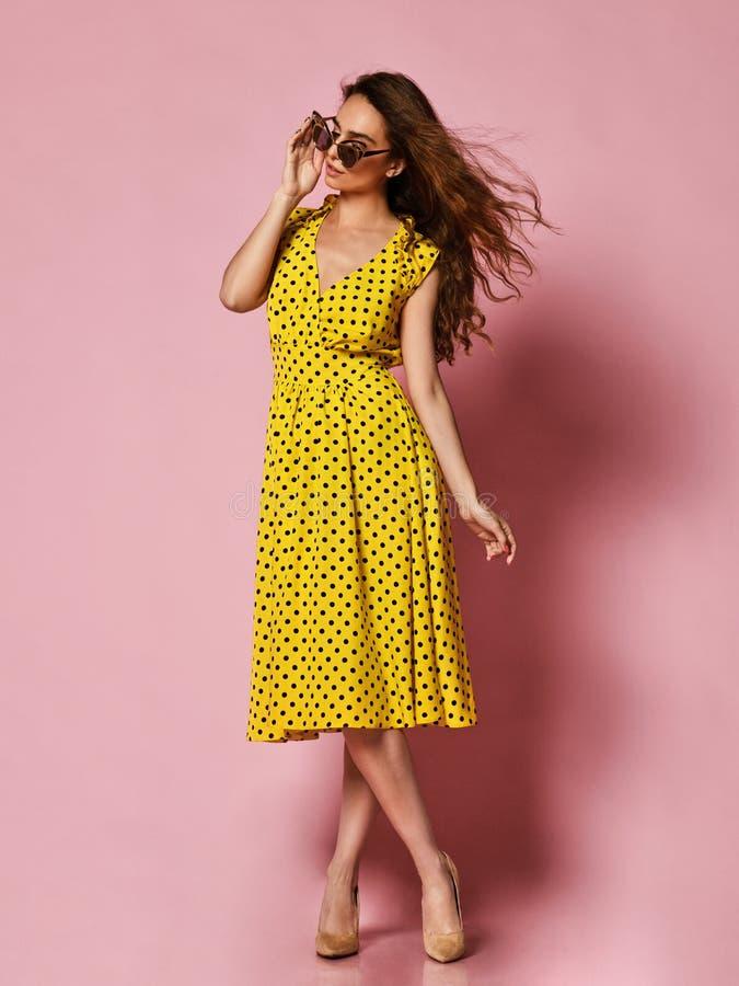 一件浪漫礼服的美女相当微笑在紫色背景的 在一件黄色圆点礼服的苗条卷曲女性模型 免版税库存图片