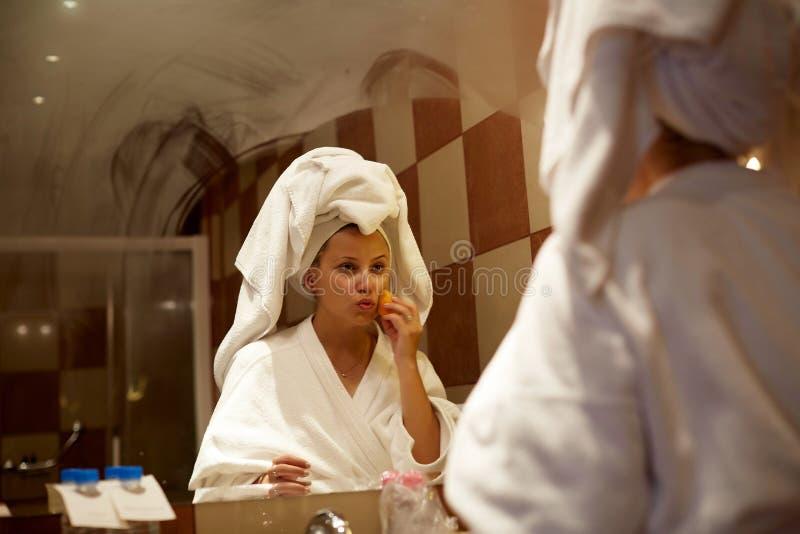 一件浴巾的女孩在一个镜子前面在做构成的卫生间里 免版税库存照片